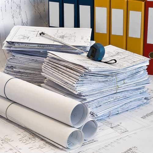 Стопки строительных чертежей, папки и рулетка